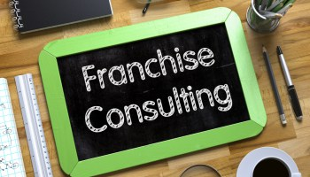 Franchise Consulting - Green Small Chalkboard with Hand Drawn Text and Stationery on Office Desk. Top View. Franchise Consulting - Text on Small Chalkboard.3d Rendering.